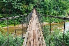 Puente colgante, cruzando el río, barcaje en el bosque, imagen de archivo libre de regalías