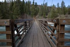 Puente colgante de madera sobre el río imagen de archivo