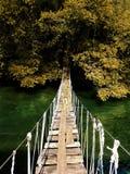 Puente colgante de madera viejo de la ejecución que cruza el río Foto de archivo libre de regalías