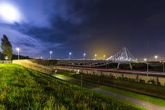 Puente colgante en la noche bajo claro de luna con los rastros ligeros imágenes de archivo libres de regalías