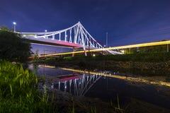 Puente colgante en la noche bajo claro de luna con los rastros ligeros foto de archivo libre de regalías