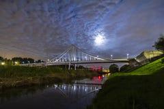 Puente colgante en la noche bajo claro de luna, reflexión en agua fotos de archivo libres de regalías