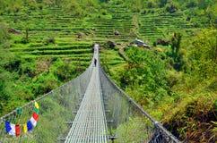 Puente colgante en montañas Himalayan Pista del campo bajo de Annapurna Fotos de archivo libres de regalías