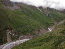Puente colgante grande en valle Himalayan seco durante monzón Fotos de archivo libres de regalías