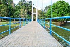 Puente colgante para caminar sobre el río en parque público Fotos de archivo