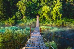 Puente colgante sobre el río en el cual la gente camina fotografía de archivo