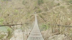 Puente colgante sobre el río en montañas en Nepal Viaje del circuito de Manaslu metrajes