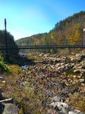 Puente colgante sobre una cama de río en otoño Foto de archivo