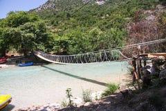 Puente colgante sobre una corriente de la montaña Imagen de archivo