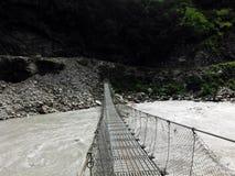 Puente colgante tradicional que cruza un río salvaje Imagen de archivo