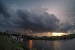 Puente con el stormcloud en la puesta del sol foto de archivo
