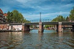 Puente con la barandilla del hierro en el canal arbolado, edificios viejos y el cielo azul soleado en Amsterdam Foto de archivo libre de regalías