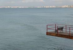 Puente con un banco que pasa por alto el mar Foto de archivo libre de regalías