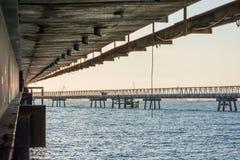 Puente concreto sobre la agua de mar con salida del sol Imagenes de archivo