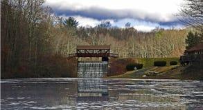 Puente cubierto y cascada con el lago reflector Imagen de archivo