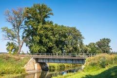 Puente de acero del ferrocarril del paisaje del campo sobre el canal del agua Foto de archivo