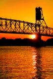 Puente de braguero con el palmo de la elevación sobre el río en la puesta del sol Foto de archivo