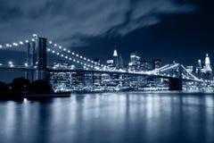 Puente de Brooklyn en Nueva York con reflexiones de las luces en el agua fotografía de archivo