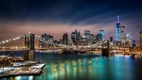 Puente de Brooklyn y el distrito financiero por noche Fotos de archivo