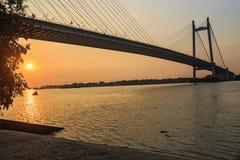 Puente de cable Vidyasagar Setu en el río Hooghly en la opinión de la silueta de la puesta del sol Foto de archivo