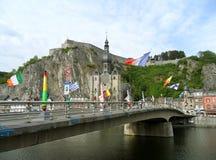 Puente de Charles de Gaulle con muchas esculturas gigantes del saxofón y la iglesia colegial de Notre-Dame en el fondo, Dinant Fotografía de archivo libre de regalías