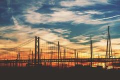 Puente de cuerda en Lisboa durante puesta del sol imponente Imagen de archivo libre de regalías