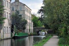 Puente de Hebden con el canal del rochdale, los barcos del camino de sirga y los edificios Imagenes de archivo