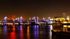 Puente de Hungerford y puentes de oro del jubileo en la noche imagen de archivo