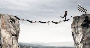 Puente de la ayuda de los hombres de negocios a conseguir a la bandera Concepto de la meta de negocio del logro Foto de archivo libre de regalías