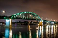 Puente de la ciudad en la noche con la reflexión en agua Imagen de archivo