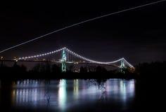 Puente de la puerta de los leones en la noche con un luz-rastro de los aviones arriba según lo visto del parque de Ambleside foto de archivo libre de regalías