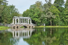 Puente de mármol en una charca grande en el parque de Catherine Tsarskoe Selo Imagenes de archivo