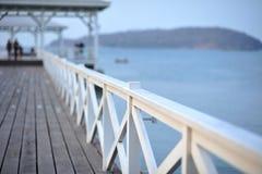 Puente de madera blanco sobre el mar y la montaña Foto de archivo