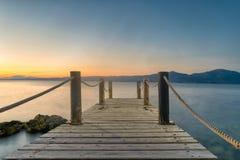 Puente de madera contra la puesta del sol y mar en Oropos en Grecia Imágenes de archivo libres de regalías