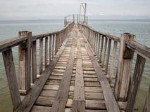 Puente de madera de la playa al mar Foto de archivo libre de regalías
