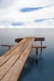 Puente de madera debajo del cielo en un océano Fotos de archivo libres de regalías