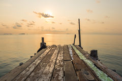 Puente de madera del embarcadero con la escena tranquila del paisaje marino durante sunri Fotos de archivo libres de regalías