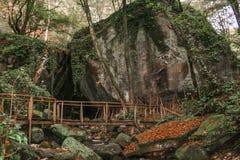 Puente de madera del paisaje misterioso de hadas en un fondo del ` de los hermanos del ` dos de las rocas Imagen de archivo libre de regalías