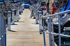 Puente de madera del puerto con los cargadores a navegar Fotografía de archivo libre de regalías