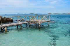 Puente de madera en agua de mar cristalina hermosa Imagenes de archivo