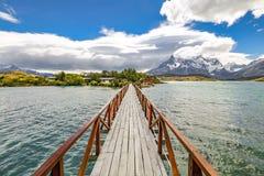 Puente de madera en el lago y las montañas grandes Nevado Imágenes de archivo libres de regalías