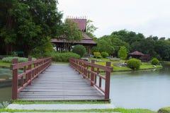Puente de madera en el parque a través del pequeño lago Imagen de archivo libre de regalías