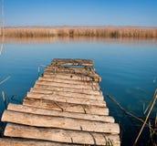 Puente de madera en el río azul Fotos de archivo libres de regalías