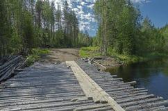 Puente de madera en un camino de tierra del bosque Imagenes de archivo