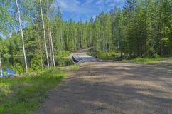 Puente de madera en un camino de tierra del bosque Fotos de archivo