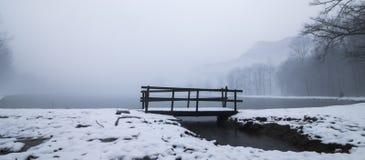 Puente de madera en un lago del invierno Foto de archivo libre de regalías