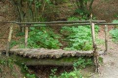 Puente de madera en una trayectoria de bosque en la manera al monasterio de la cueva en las colinas cárpatas Rozhirche Fotos de archivo libres de regalías