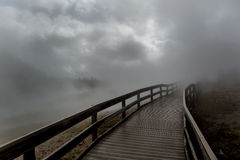 Puente de madera engullido en niebla fotos de archivo