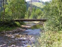 Puente de madera sobre el río de la montaña Foto de archivo libre de regalías