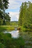 Puente de madera sobre el río del bosque en un día de verano Fotos de archivo